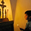 A boy lights a candle during a Palm Sunday service in Veliky Novgorod