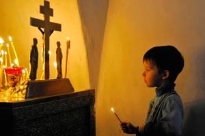 A boy lights a candle during a Palm Sunday service in Veliky Novgorod